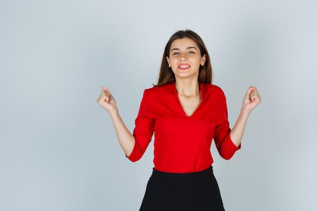 Jovem de blusa vermelha, saia mostrando gesto de vencedor e parecendo feliz