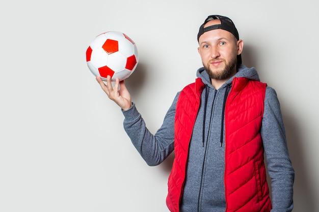 Jovem de boné, moletom com capuz e colete segura uma bola na mão contra uma parede de luz