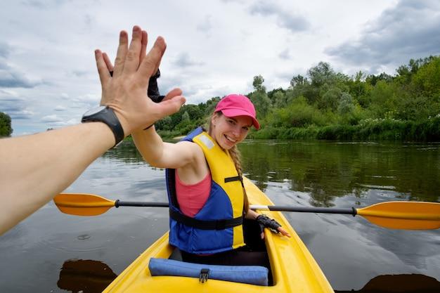 Jovem de boné rosa remar em caiaque sobre o rio, dando mais cinco para seu companheiro de equipe