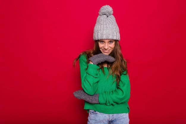 Jovem de cabelos compridos com suéter verde e boné de malha cinza rindo no vermelho