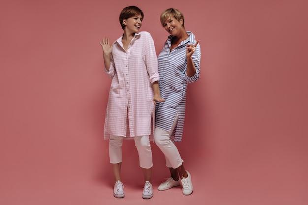 Jovem de cabelos curtos em camisa rosa e calças leves, sorrindo e posando com uma mulher loira em roupas azuis listradas em pano de fundo isolado.