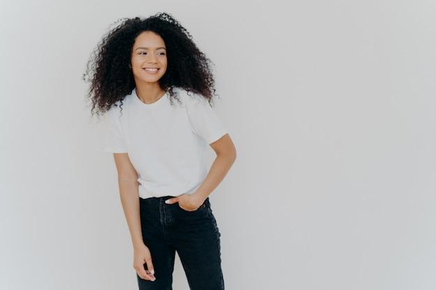 Jovem de cabelos encaracolada tem figura esbelta, veste jeans e camiseta branca, olha de lado com expressão feliz