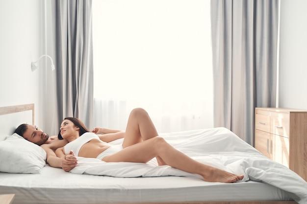 Jovem de cabelos escuros em lingerie deitada na cama sobre o peito do jovem marido