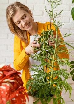 Jovem de camisa amarela fazendo jardinagem em casa