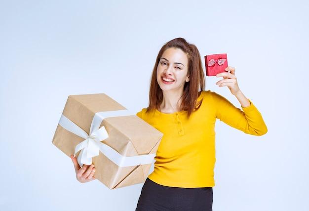 Jovem de camisa amarela segurando uma caixa de presente vermelha e outra de papelão