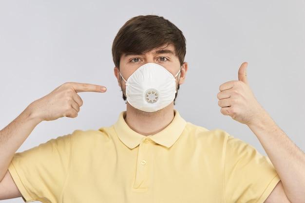 Jovem de camisa amarela usa máscara respiratória de proteção contra coronavírus e mostra um gesto de polegar para cima