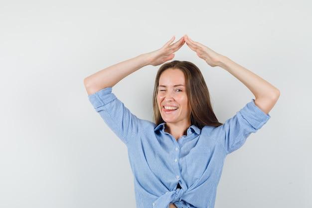Jovem de camisa azul fazendo gesto de telhado de casa acima da cabeça e parecendo alegre
