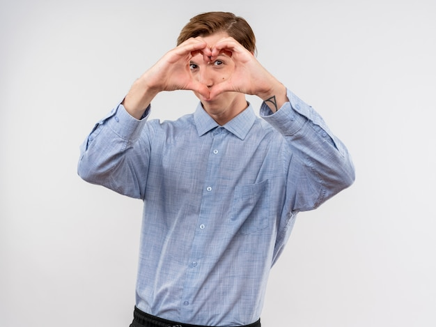 Jovem de camisa azul fazendo um gesto com os dedos, olhando para a câmera com os dedos em pé sobre um fundo branco