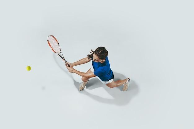 Jovem de camisa azul jogando tênis. estúdio interno, tiro isolado no branco. vista do topo.