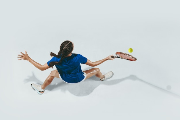 Jovem de camisa azul jogando tênis. vista do topo.