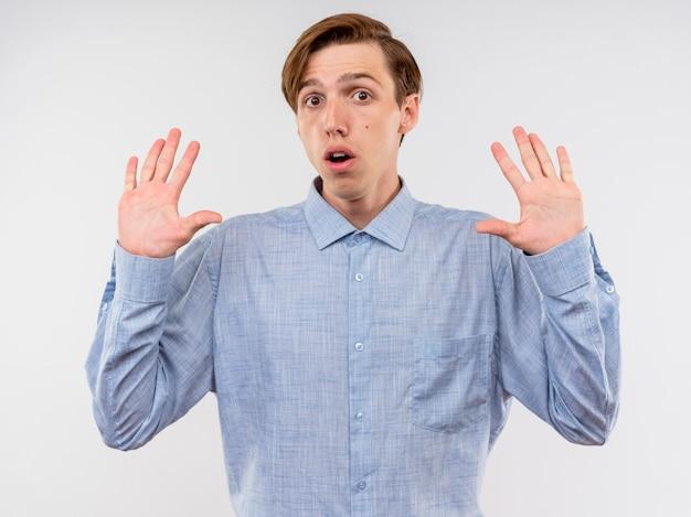 Jovem de camisa azul levantando as mãos em sinal de rendição com medo em pé sobre um fundo branco