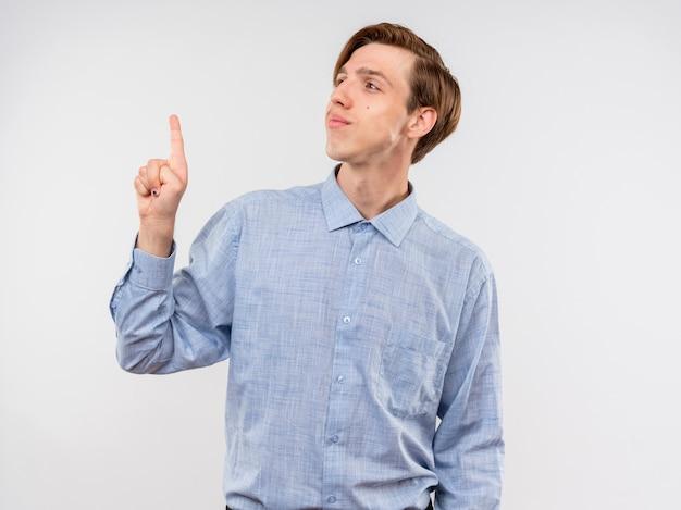 Jovem de camisa azul olhando de lado apontando para algo com o dedo indicador sorrindo confiante em pé sobre um fundo branco