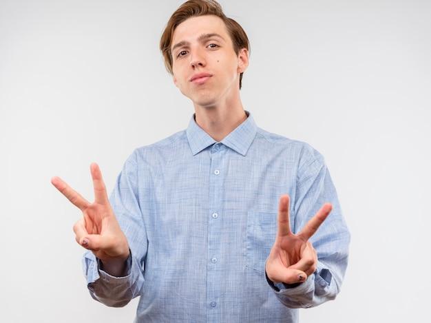 Jovem de camisa azul olhando para a câmera com um sorriso no rosto mostrando a placa de vídeo em pé sobre um fundo branco