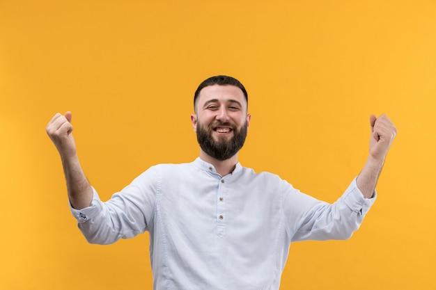 Jovem de camisa branca com barba com as mãos levantadas