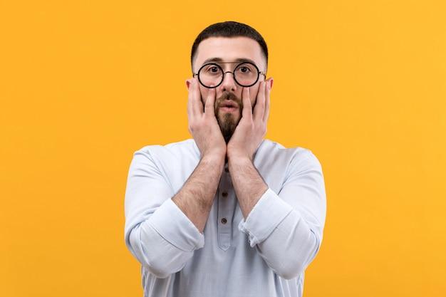 Jovem de camisa branca com barba e óculos com expressão de surpresa