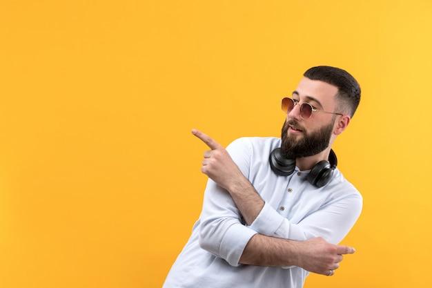 Jovem de camisa branca com barba, óculos escuros e fones de ouvido pretos
