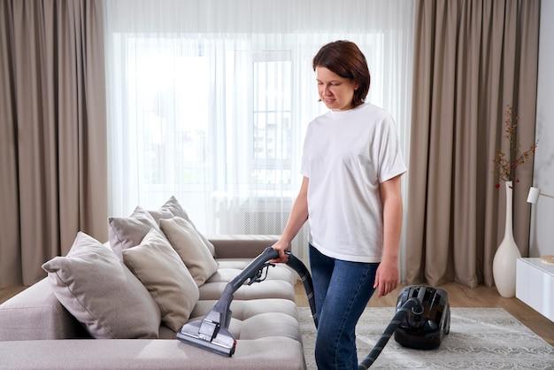 Jovem de camisa branca e jeans, limpeza do tapete sob o sofá com aspirador de pó na sala de estar, copie o espaço. conceito de trabalho doméstico, limpeza e tarefas domésticas