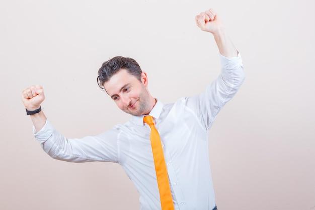 Jovem de camisa branca, gravata, mostrando o gesto do vencedor e parecendo feliz