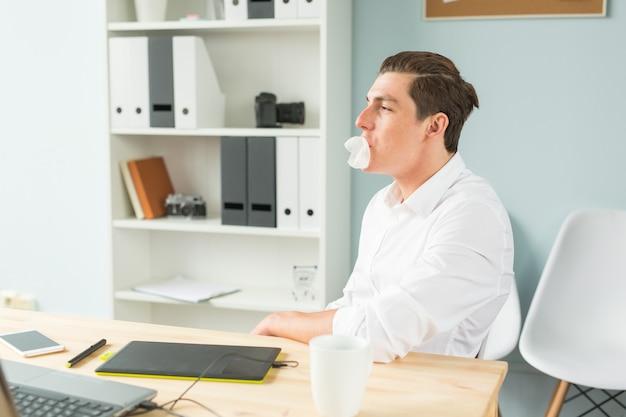 Jovem de camisa branca mascando chiclete no escritório