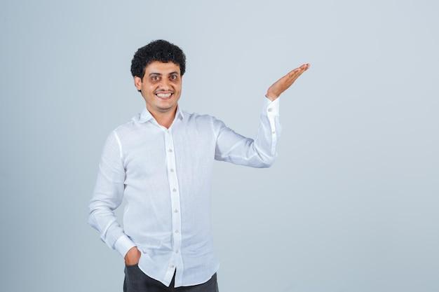 Jovem de camisa branca, mostrando algo acima ou dando boas-vindas e parecendo alegre, vista frontal.