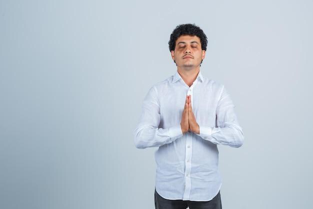 Jovem de camisa branca, mostrando o gesto de namastê e olhando em paz, vista frontal.