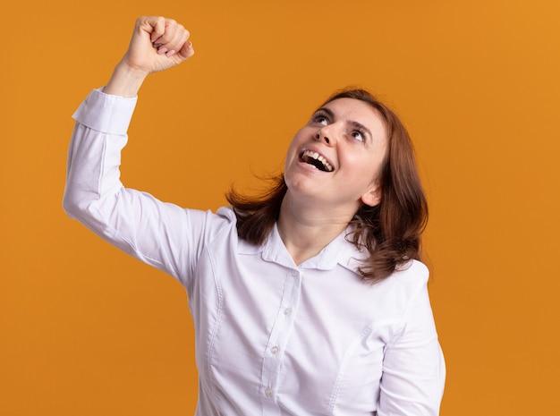 Jovem de camisa branca olhando para cima feliz e animada, levantando o punho como uma vencedora em pé sobre uma parede laranja
