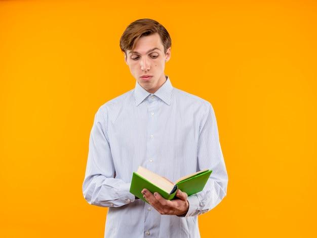 Jovem de camisa branca segurando um livro aberto e olhando para ele lendo com expressão cética em pé sobre um fundo laranja
