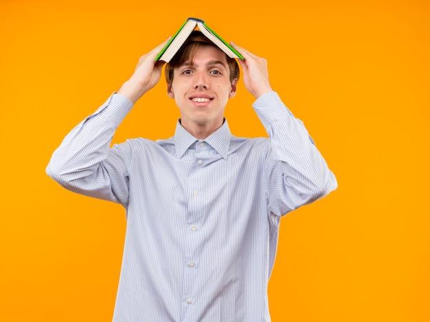 Jovem de camisa branca segurando um livro aberto sobre a cabeça e sorrindo alegremente em pé sobre uma parede laranja