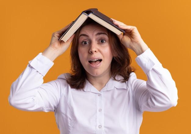 Jovem de camisa branca segurando um livro aberto sobre a cabeça e sorrindo confusa em pé sobre uma parede laranja