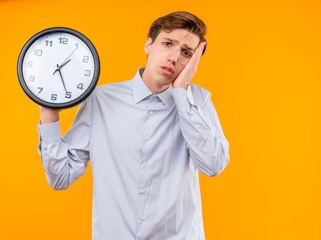 Jovem de camisa branca segurando um relógio de parede, parecendo confuso com uma expressão triste em pé sobre a parede laranja