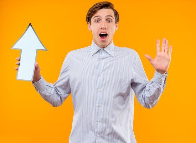 Jovem de camisa branca segurando uma seta azul, olhando para a câmera, surpreso e feliz com a mão levantada em pé sobre um fundo laranja
