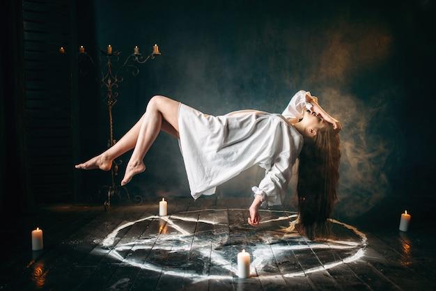 Jovem de camisa branca voando sobre o círculo do pentagrama, magia gark, ritual de sacrifício. ocultismo e exorcismo
