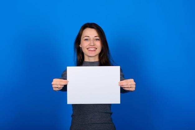 Jovem de camisa cinza, segurando uma folha de papel e olhando para a câmera, sorrindo. parede azul isolada