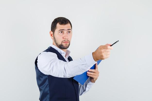 Jovem de camisa, colete apontando para longe, segurando a prancheta e parecendo sensato