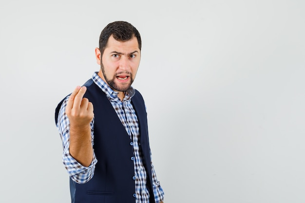 Jovem de camisa, colete, tentando explicar algo e parecendo com raiva, vista frontal.