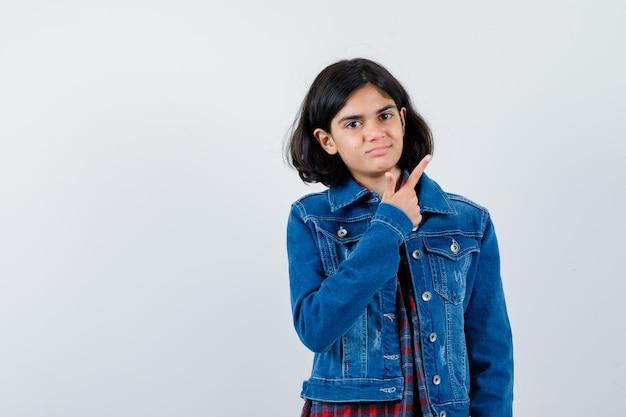 Jovem de camisa e jaqueta jeans apontando para a direita com o dedo indicador e olhando séria, vista frontal.