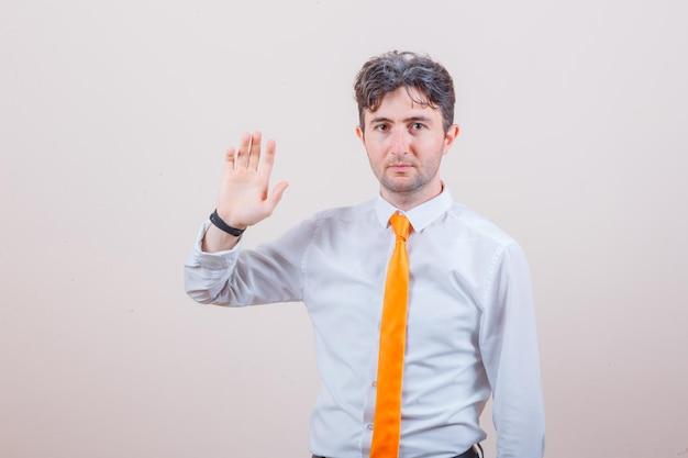 Jovem de camisa, gravata, acenando com a mão para se despedir