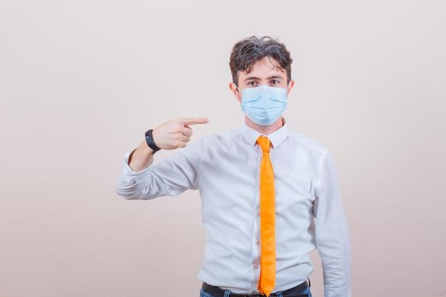 Jovem de camisa, gravata e jeans apontando para sua máscara médica