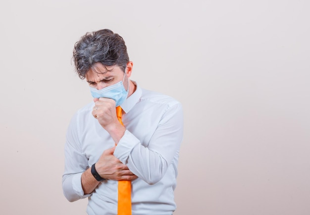 Jovem de camisa, gravata e máscara, sofrendo de tosse e parecendo indisposto