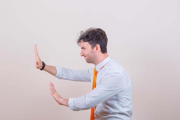 Jovem de camisa, gravata mantendo as mãos de forma preventiva e parecendo irritado.