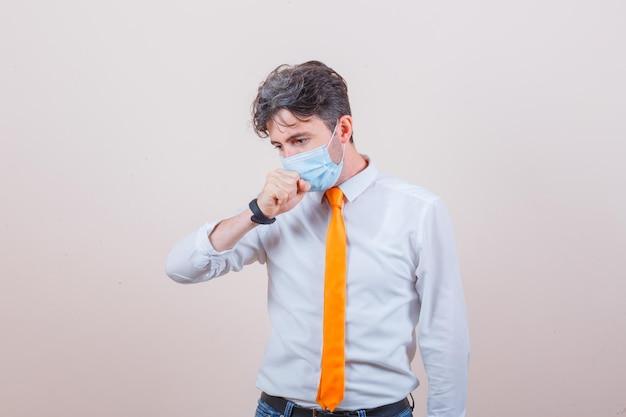 Jovem de camisa, gravata, máscara, jeans, sofrendo de tosse e parecendo indisposto