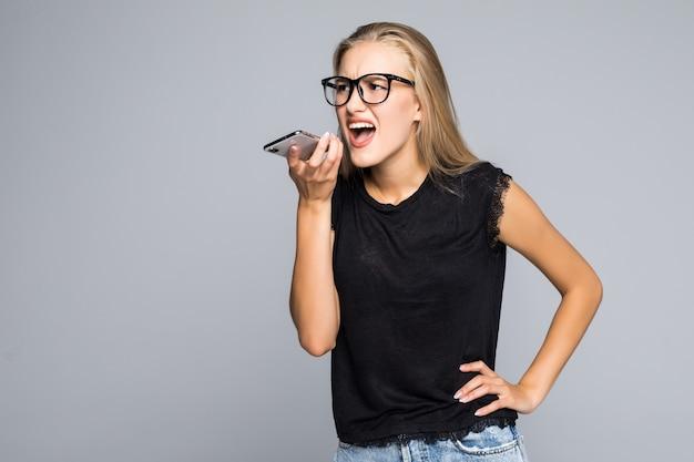 Jovem de camisa gritando no telefone isolado em fundo cinza
