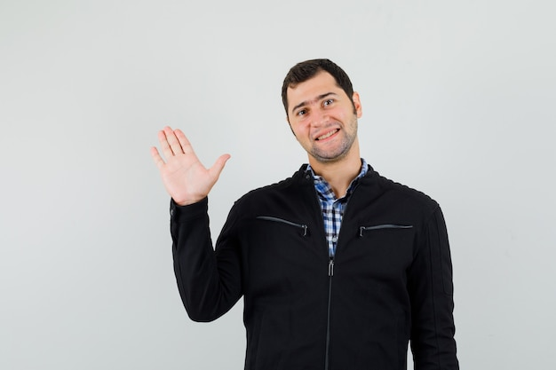 Jovem de camisa, jaqueta, acenando com a mão para se despedir e parecendo alegre