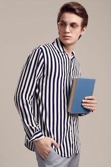 Jovem de camisa listrada, posando com um livro sobre fundo cinza