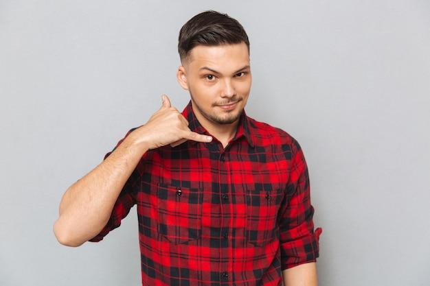 Jovem de camisa mostrando sinal de telefone