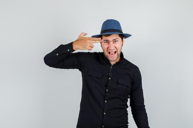 Jovem de camisa preta, chapéu fazendo gesto de suicídio e gritando