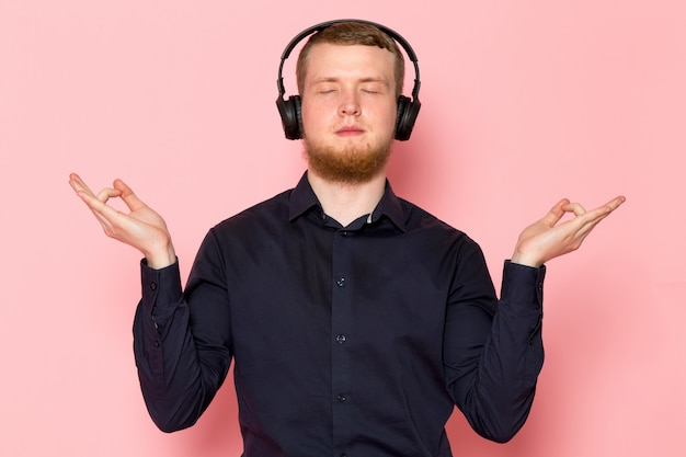 Jovem de camisa preta com fones de ouvido pretos