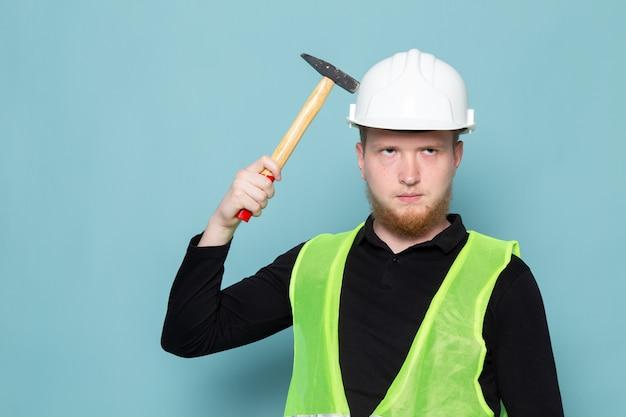 Jovem de camisa preta e colete verde construção segurando o martelo