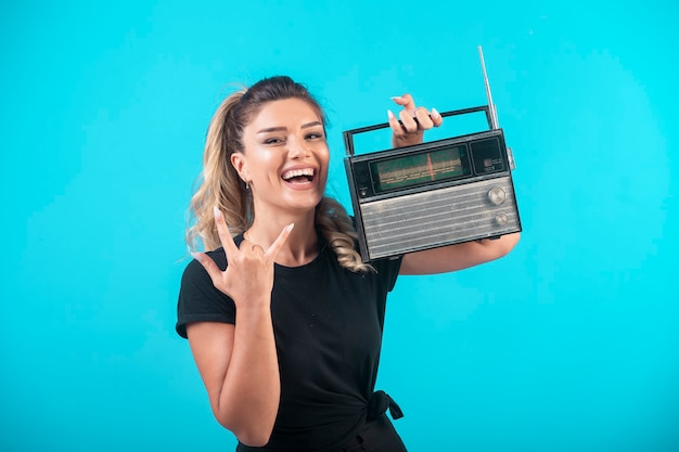 Jovem de camisa preta, segurando um rádio vintage no ombro e se sente positiva.