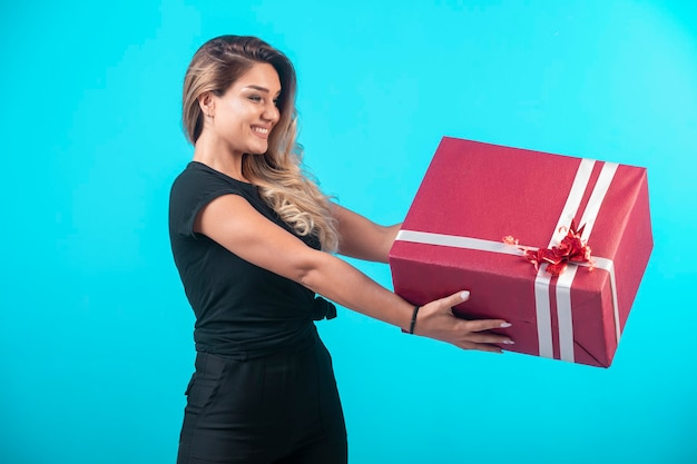Jovem de camisa preta segurando uma caixa de presente grande e se sente positiva.
